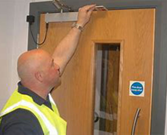 An inspector inspecting a fire door. Fire Door Inspection at Select Safety Services Essex